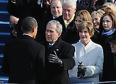 Washington, DC - January 20, 2009 -- United States President Barack Obama (L) is hugged by former President George W. Bush after Obama  was sworn-in as the 44th President of the United States on the west steps of the Capitol on Tuesday, January 20, 2009. Also shown are former President Bill Clinton (top), Sen. Hillary Clinton and Laura Bush.  .Credit: Pat Benic - Pool via CNP