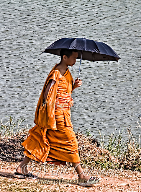A young monk goes about his daily duties, his umbrella providing a shield from the heat of the midday sun.<br /> (Photo by Matt Considine - Images of Asia Collection)