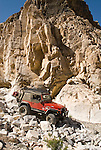 A red jeep with the Motherlode Rock Crawlers travels down a rock-piled road in the Argus Range of California.