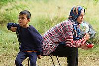 SERBIEN, 08.2016, Kelebija. Internationale Fluechtlingskrise: An der mit Zaeunen abgesperrten ungarischen Grenze stauen sich Fluechtlinge und Migranten. Sie bitten meist vergebens um Einlass in die  Asyl- und Transitzonen (blaue Container). So haben sich auf serbischer Seite provisorische Lager mit sehr schlechten Bedingungen gebildet. | International refugee crisis: Refugees and migrants have been piling up at the fenced-off Hungarian border. They are waiting for entrance into the asylum and transit zones (blue containers), mostly in vain. Thus provisional camps have emerged on the Serbian side with very bad conditions. In the picture Noor Mahmud and Ahmed Mahmud.<br /> © Szilard Vörös/EST&OST
