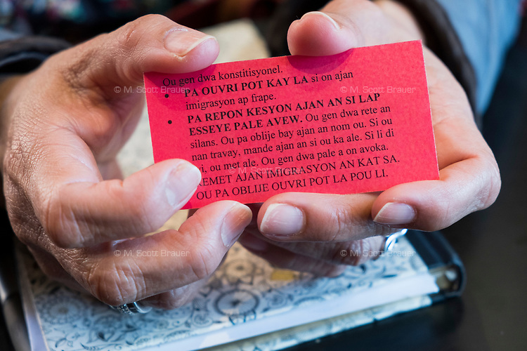 """Isabel Lopez, 50, of Hyde Park, Boston, Massachusetts, holds a card given out to area immigrants as part of """"Know Your Rights"""" efforts by advocates of immigrants. Lopez is an independent community organizer who has worked with various organizations in the Brockton, Massachusetts, area for the past 8 years. The card has information about people's constitutional rights and what to say if immigration enforcement officers come to one's home. On one side is English, and on the other side is Haitian-Creole."""