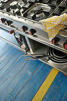 Detail of part of a large stainless steel range in the kitchen which stands on blue painted floorboards decorated with a single yellow stripe