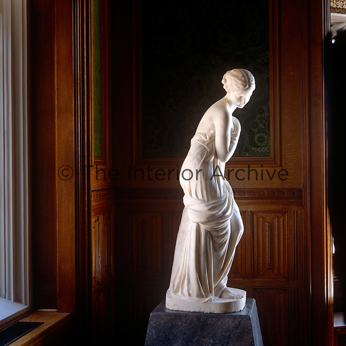 A white marble statue in the Lord Chancellor's apartments appears to glow against the dark, gothic background of the panelled walls
