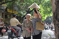 Hanoi<br /> , Vietnam - 2007 File Photo -<br /> <br /> A woman use a traditional hat to cover an old Vietnames lady as they walk under the sun  in Hanoi street.<br /> <br /> <br /> <br /> photo : James Wong-  Images Distribution