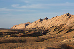 Tongues of the darker Carmel Formation mudstone protrude up like jagged teeth over the whiter Navajo Sandstone at the base of the San Rafael Reef in south central Utah.  San Rafael Reef BLM WIlderness Study Area.  In the distance are the sno-capped Henry Mountains.