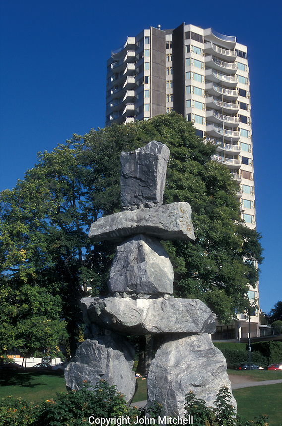 Inuit Inukshuk in front of a modern highrise apartment building in Vancouver, British Columbia, Canada