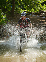 NWA Democrat-Gazette/BEN GOFF @NWABENGOFF<br /> Jacob Smithpeters, a category 3 racer from Rogers, fords a creek Sunday, July 16, 2017, during cross country races on the final day of the 19th annual Fat Tire Festival at Lake Leatherwood City Park in Eureka Springs.