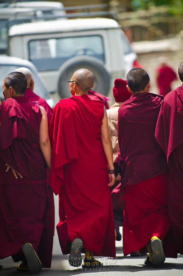 Young Buddhist monks wearing red robes walk along the street in Leh, Ladakh, India.