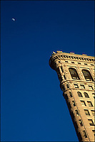 Side view of Flatiron Building with Moon agaist a deep blue sky.