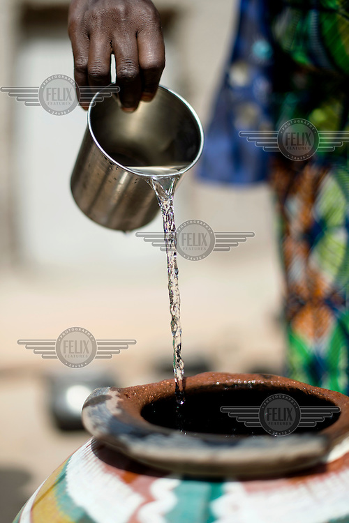 A woman pouring water into an earthenware container in the village of Din-Rimi.