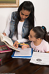 9 year old girl at home with mother, doing homework with her support