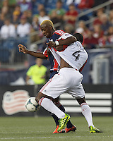 New England Revolution forward Dimitry Imbongo (92) attempts to control the ball as New England Revolution midfielder Kalifa Cisse (4) closely defends. In a Major League Soccer (MLS) match, Toronto FC (white/red) defeated the New England Revolution (blue), 1-0, at Gillette Stadium on August 4, 2013.