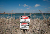 A sign warns against swimming in treated water at a holding lake at a Fountain Quail water management  and treatment facility in Roanoake, Texas, Tuesday, February 16, 2011. Fountain Quail cleans and separates water used in fracking for natural gas removal...Photo by Matt Nager