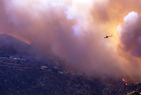 870000387 a los angeles county fire fighting helicopter flies above hillside homes and a burning hillside in the path of the topanga fire in the hills above the san fernando valley in southern california