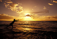 Throw net fisherman frames the sun with his net at Kihei, Maui,