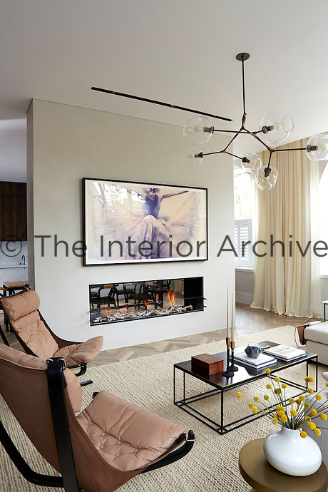 A neutral palette in the living room creates a timeless design. Bespoke upholstery and subtle and unfussy furniture complete the elegant look. An open fireplace provides a stylish focal point in the room.
