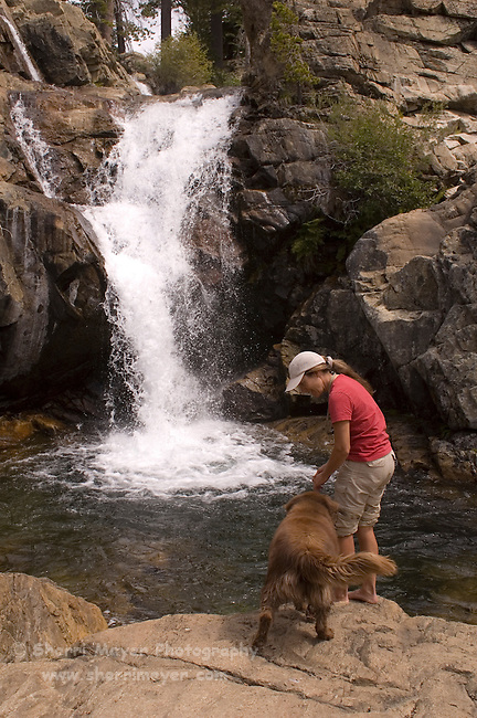 Woman hiker and her dog checking out a swimming hole on Canyon Creek, Tahoe National Forest California