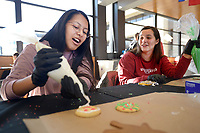 NWA Democrat-Gazette/ANDY SHUPE<br /> Claire Riddell (left), an undergraduate student from Kansas City, Mo., and friend Jennifer Beyard, a student from Fort Worth, Texas, laugh Wednesday, Dec. 5, 2018, as they decorate cookies in the Connections Lounge in the Arkansas Union on the University of Arkansas campus in Fayetteville. The event, which is organized by Chartwells, is a stress-reliever for students who get to decorate two cookies, one to keep and one to donate to members of the campus community in need through the Full-Circle Food Pantry. Extra cookies will be donated to the Yvonne Richardson Community Center, LifeSource International and the Salvation Army.