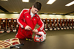 Wisconsin Badgers student manager Alex Graf screws on a face mask in the team locker room prior to the 2012 Rose Bowl NCAA football game against the Oregon Ducks in Pasadena, California on January 2, 2012. The Ducks won 45-38. (Photo by David Stluka)