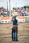 A cowboy stands in the arena before the rodeo, watching the excited public.
