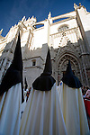 Hooded penitents entering Seville's cathedral on Holy Monday, Spain