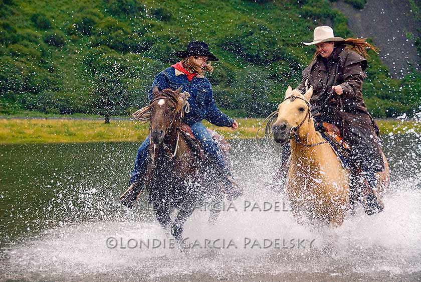 Cowgirls running horse in the Pasagshak River, Kodiak Island, Alaska