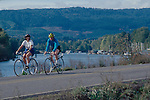 Portland, Sauvie Island, Columbia River, Oregon, Couple bicycling past river, Pacific Northwest, USA,