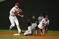 Isiah Gilliam (25) of the Charleston RiverDogs is out as second baseman Brett Netzer (12) of the Greenville Drive turns a double play following a flip from shortstop Santiago Espinal (2), right, in Game 3 of the South Atlantic League Southern Division Playoff against the Charleston RiverDogs on Saturday, September 9, 2017, at Fluor Field at the West End in Greenville, South Carolina. Greenville won, 5-0, winning the division championship two games to one. (Tom Priddy/Four Seam Images)