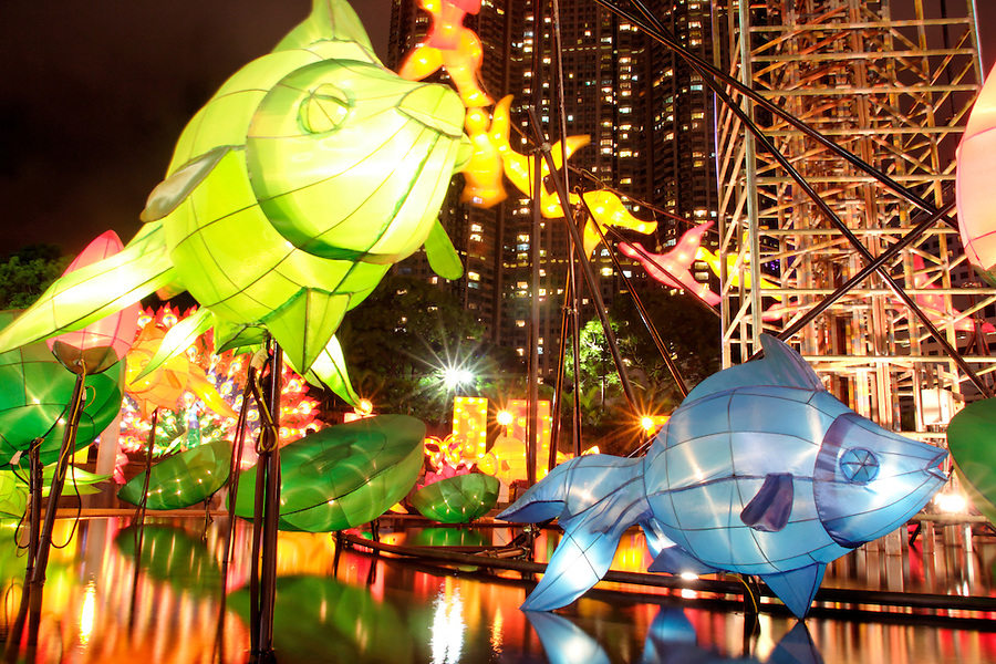 Illuminated fish and flower lanterns above pond displayed in celebration of Mid-Autumn Festival, Kowloon Park, Tsim Sha Tsui, Kowloon, Hong Kong SAR, China, Asia