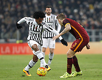 Juventus' Juan Cuadrado, left, is challenged by Roma's Lucas Digne during the Italian Serie A football match between Juventus and Roma at Juventus Stadium.