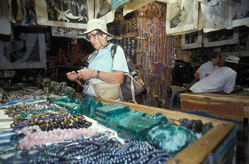 A western tourist in  a tourist shop on the borders of the Maasai Mara. Kenya. The majority ofthe articles on sale  have not come from maasai villages but are mass produced by Kikuyu tradesmen.