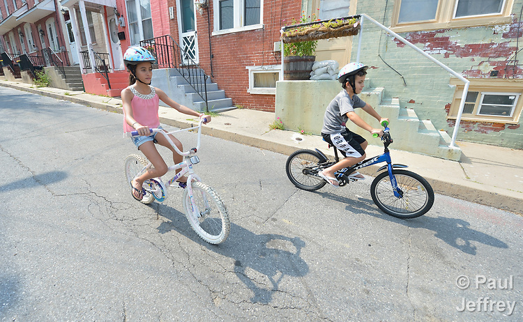 Elianys Curino and her brother Enmanuel ride their bikes on the street near their home in Lancaster, Pennsylvania. Refugees from Cuba, they and their family were resettled in Lancaster by Church World Service. <br /> <br /> Photo by Paul Jeffrey for Church World Service.