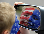 James Szemreylo, 7, of Tolland, looks at the red white and blue face painting just completed by his mother, Colleen, in the door  mirror of the family van, Tuesday, July 3, 2012, getting ready for the annual July 4th kids parade in Rockviile, during Vernon's July 4th celebration. (Jim Michaud/Journal Inquirer)