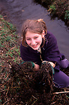 AE2BX2 Young girl helping to clear weeds from a  stream