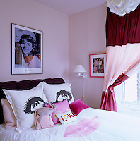 This teenage girl's bedroom has pale pink walls and curtains made of three shades of Indian silk