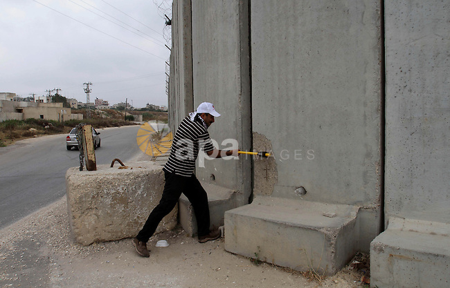 A Palestinian protester uses sledgehammers to break parts from a concrete segment of a separation wall in the West Bank city of Tulkarem, 31 May 2014. Reportedly dozens of Palestinians were injured during clashes with Israeli forces that erupted after protesters tried to damage and remove parts of the Israeli separation wall during a march to support Palestinian prisoners in Israeli jails. Photo by Nedal Eshtayah