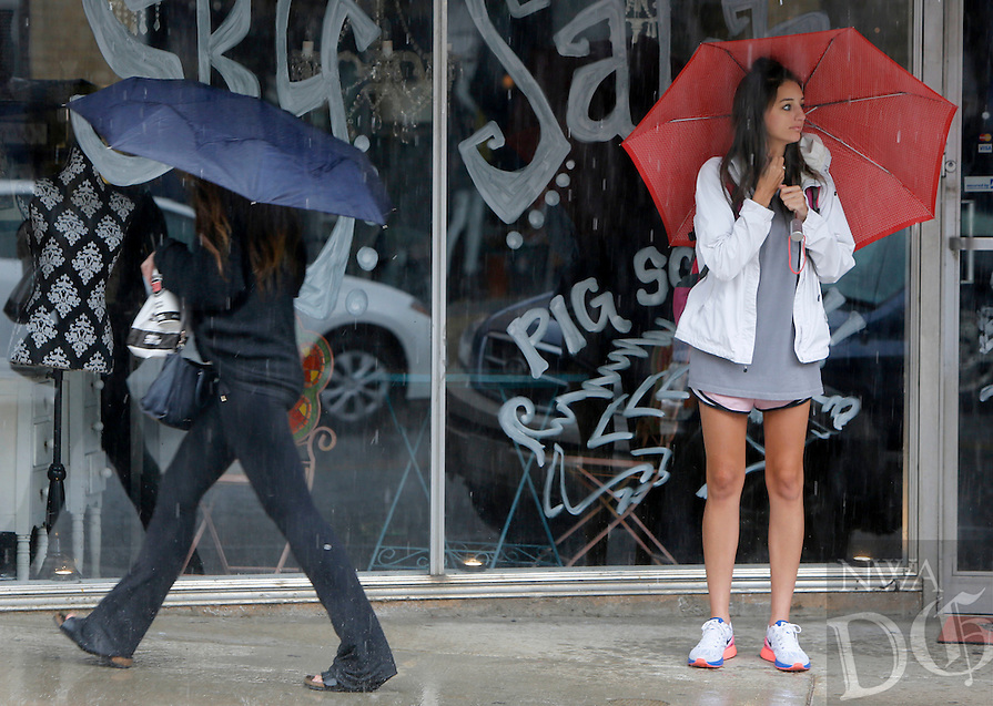 NWA Media/DAVID GOTTSCHALK - 10/2/14 - Paige Thompson, right, of Fayetteville, pauses under an awning and umbrella during an afternoon rain shower Thursday October 2, 2014 on Dickson Street in Fayetteville. Rain was forecasted for the area running into the evening and clearing out by today.