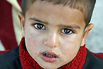 The confusion is evident in this child's eyes as Iraqi troops search his family's home in the village of Al Cheb Allib, Iraq. Iraqi soldiers backed by U.S. advisors were looking for insurgents and weapons, but they found neither, and villagers generally welcomed the troops' presence. Nov. 29, 2007. DREW BROWN/STARS AND STRIPES