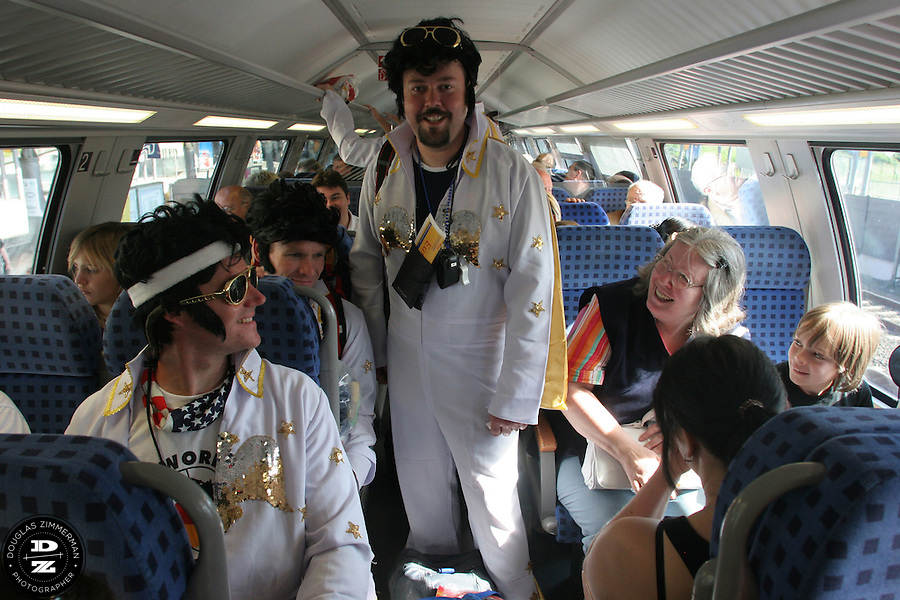 """USA National Soccer Team fans, (left to right) Barry Ryan of Kansas City, MO, Pat Ryan of Kansas City, MO, and Philippe Lechevin of Kansas City, MO, dressed up in flight suits as the American Icon Elvis, were greeted with smiles by fellow travelers aboard the express train from the Düsseldorf Airport train station to Cologne, Germany. The group was traveling by train to Cologne, Germany and their hotel. They arrived at Düsseldorf Airport in Germany on Saturday morning, June 10th, 2006 after an overnight flight from JFK airport in New York City.  The fans were part of a tour group, called """"2006 World Cup Trip"""" arraigned by Pat Ryan from Kansas City, MO by his travel company """"Ryan Adventures. They were among the thousands of American fans who have descended on Germany to support the USA National team during the 2006 FIFA World Cup. The first game for the USA is against the Czech Republic in Gelsenkirchen on Monday June 12th...For a website of the tourgroup:..http://www.2006worldcuptrip.com/..Pat Ryan can also be reached by cell phone with any questions 1.913.963.7168"""
