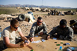 From left, Sargeants Gregory Funk, William Holt, and Deandre Strange of the 82nd Airborne's artillery platoon pass the time playing cards at Forward Operating Base Diablo in the Ghokar Valley, Kandahar province, Afghanistan on Thursday, March 22, 2007.