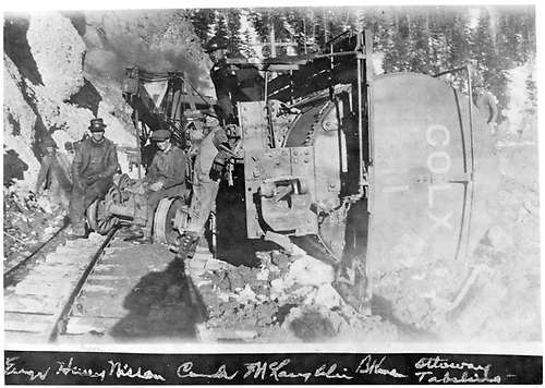 COLX tank car #11 on its side at Phantom Curve with the wrecking crew &amp; derrick standing by to work on it.<br /> D&amp;RG  Phantom Curve, CO  4/1919