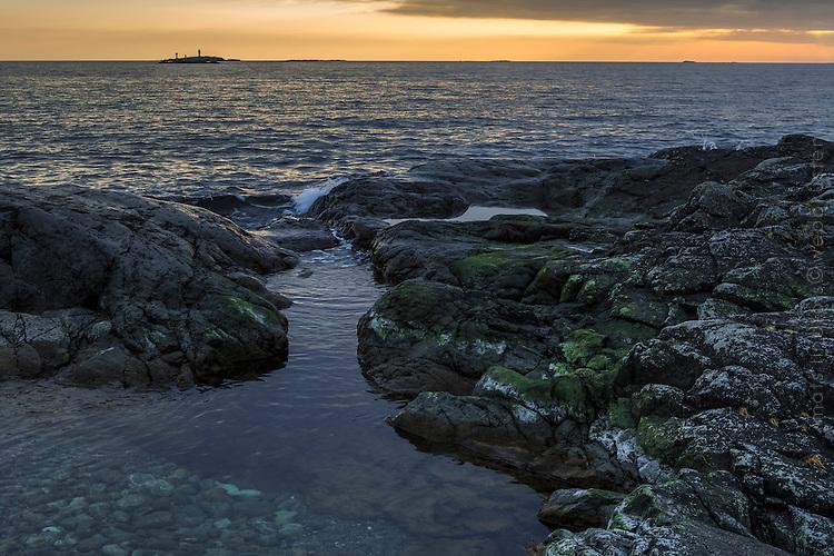 Bister klippa vid havet i skymning med horisonten på Torö i Stockholms skärgård.