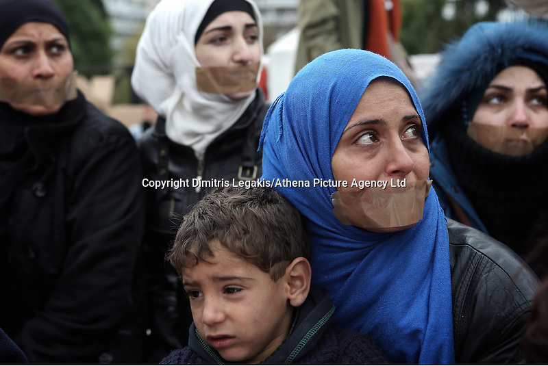 Athens Greece Monday 24 November 2014<br /> Pictured: A Syrian woman with tape over her mouth is visibly upset, clutching her young son while on hunger strike in Athens, Greece<br /> Re: More than 200 Syrian refugees are on a sixth day of a hunger strike in Athens seeking asylum and medical assistance amid a growing influx of migrants from the war-torn country, weighing on Greece's already stretched social services.<br /> In a peaceful protest that started six days ago, men, women and children wrapped in blankets have camped out on the pavement opposite Parliament in central Athens, sleeping on cardboard boxes and sleeping bags.