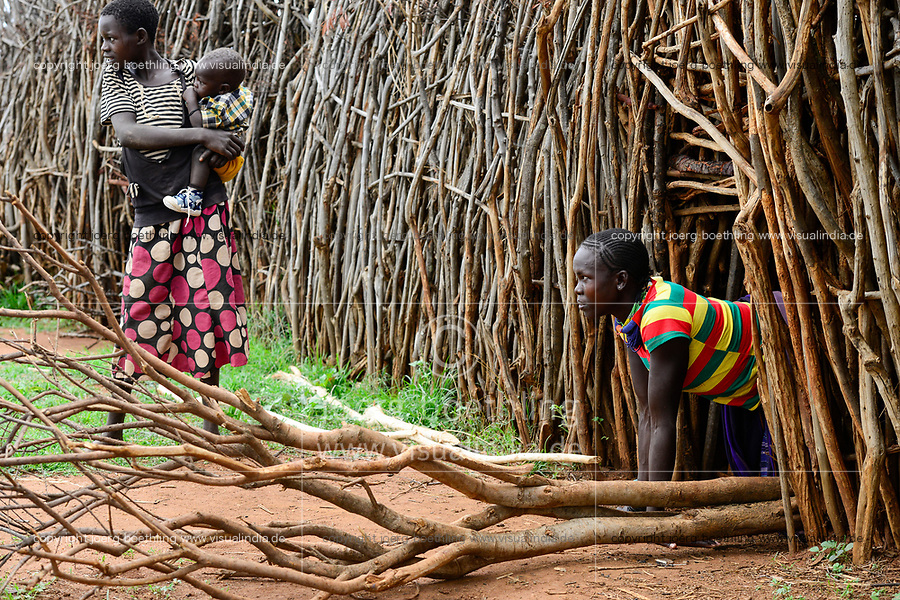 UGANDA, Karamoja, Kaabong, Karamojong tribe, Lochom village, Primina Sunday Nalamaba, 22 years, at entrance of the stick fenced village to protect the home from hostile tribes and cattle raider