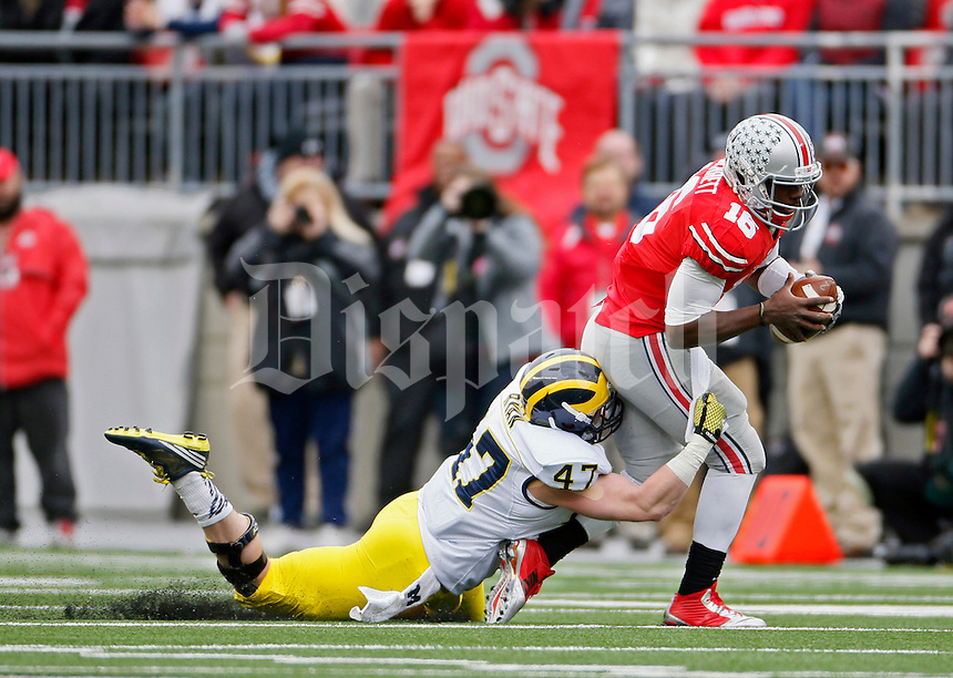 Ohio State Buckeyes quarterback J.T. Barrett (16) gets sacked by Michigan Wolverines linebacker Jake Ryan (47) in the 2nd quarter of their game at Ohio Stadium in Columbus, Ohio on November 29, 2014.  (Dispatch photo by Kyle Robertson)