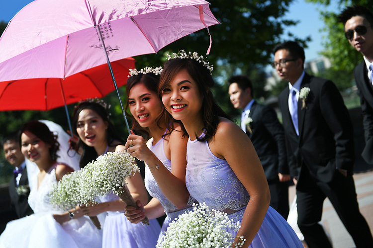 UNITED STATES - JULY 8: A wedding party from Springfield, Va., gathers for photos on the West Front of the Capitol on July 8, 2018. The groom, Truc Tran, and bride, Uyen Nguyen, are seen at left. (Photo By Tom Williams/CQ Roll Call)