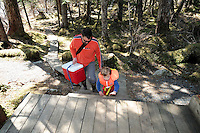 Dug Huntman helps his young son, Sam up the steps to Decision Cabin, in Decision Point State Marine Park, in Squirrel Cove, off Passage Canal, Prince William Sound, Southcentral Alaska, near Whitter, on a sunny spring afternoon in mid-May. MR