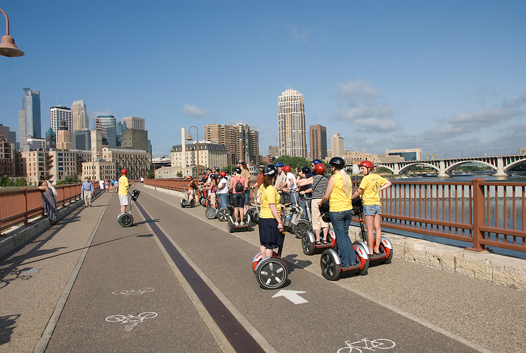 Minnesota, Twin Cities, Minneapolis-Saint Paul: Stone Arch Bridge crosses Mississippi at Minneapolis.  Former railroad bridge now used for recreation.  Segways on Stone Arch Bridge..Photo mnqual259-75162..Photo copyright Lee Foster, www.fostertravel.com, 510-549-2202, lee@fostertravel.com.