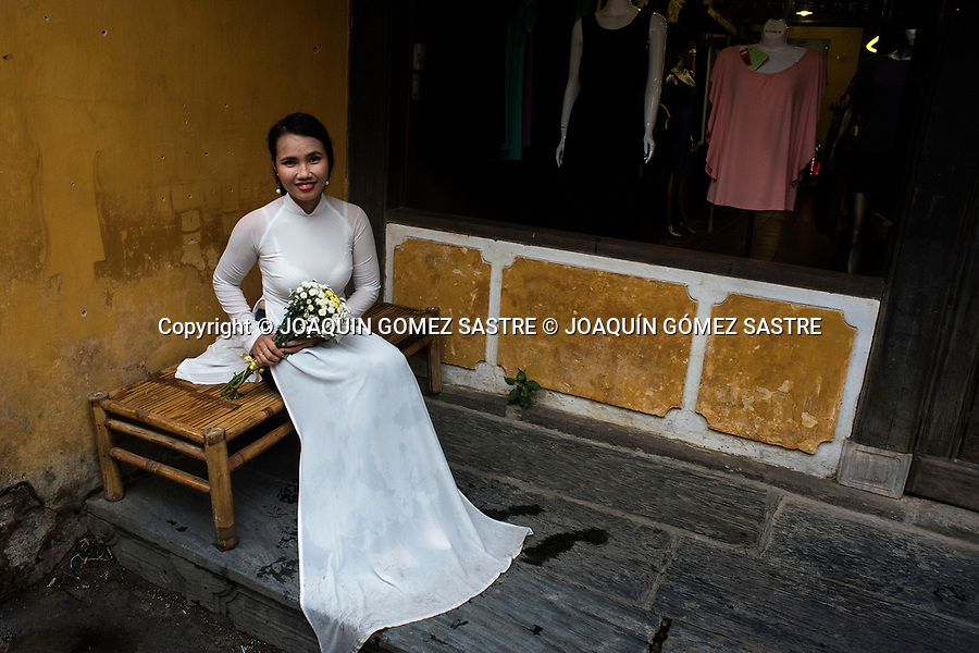 A girl in a wedding dress poses in the ancient city of Hoi An (Vietnam)