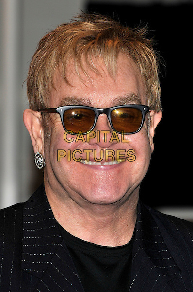 """ELTON JOHN.Photocall to open pop up shop 'Out The Closet"""" selling clothes from Elton John and David Furnish's wardrobes in aid of the Elton John AIDS Foundation, London, England.  .December 11th, 2009.fashion headshot portrait sunglasses shades silver earrings smiling.CAP/PL.©Phil Loftus/Capital Pictures."""